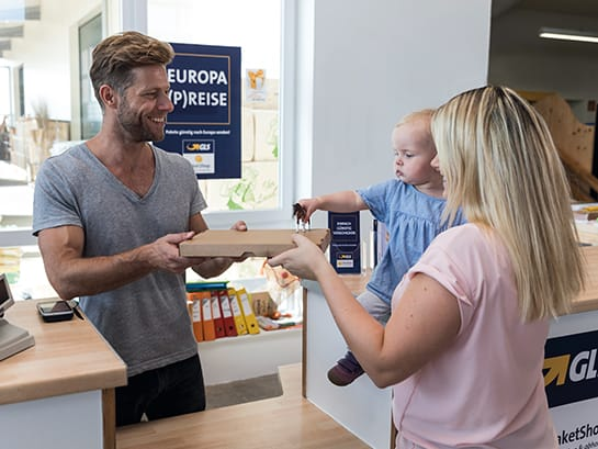 Managing a GLS ParcelShop – a man hands over a parcel to a woman with a baby