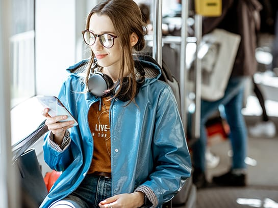 FlexDeliveryService – a woman selects a desired date & a desired location for the parcel delivery with her mobile phone while being in the streetcar