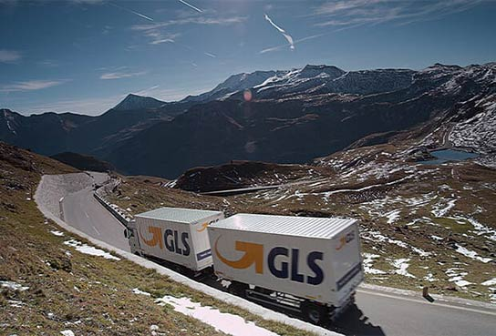 Europe-wide express delivery – a truck of the GLS parcel service drives on a road in the mountains