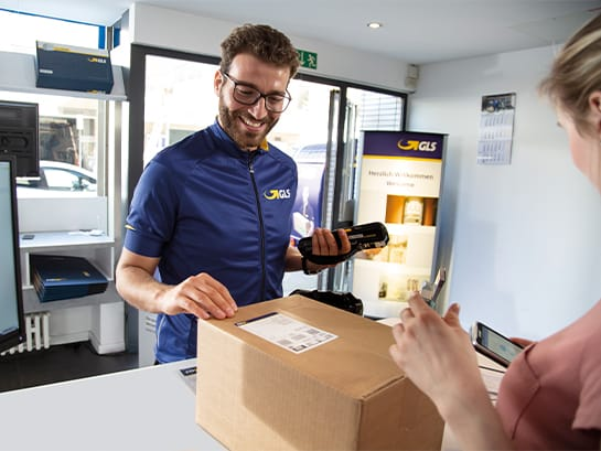 A GLS employee receives a parcel from a customer in a ParcelShop